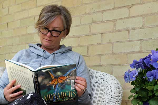 Woman Reading the Book Monarchs In A Changing World