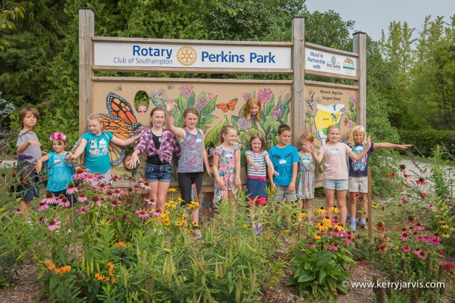 Kids standing in front of the BGOSS mural at Perkins Park