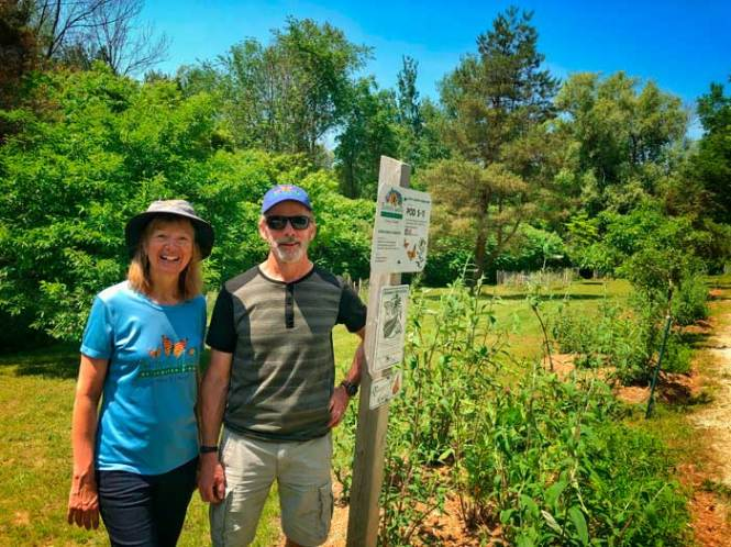 Melitta and Doug standing infront of the sign post for Butterfly Gardens of Saugeen Shores