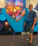Kerry Jarvis standing by migration mural